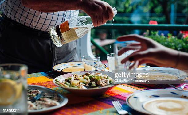 man pouring white wine into a glass - emilia romagna stock photos and pictures