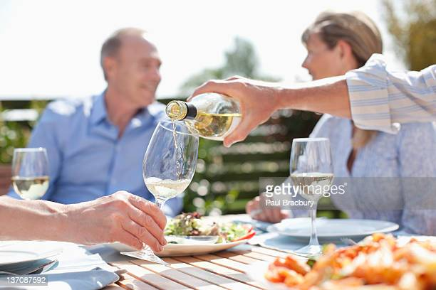 man pouring wine at sunny table - white wine stock pictures, royalty-free photos & images