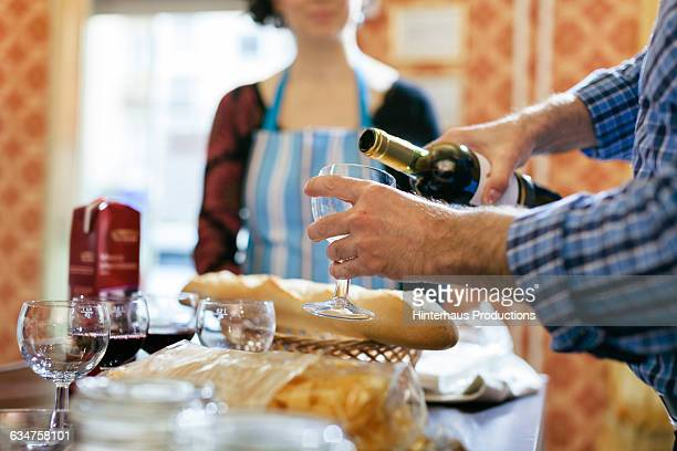 Man pouring wine in a cooking class