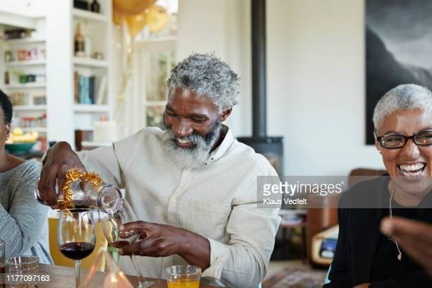 man pouring wine in glass at home during christmas - mid volwassen stockfoto's en -beelden