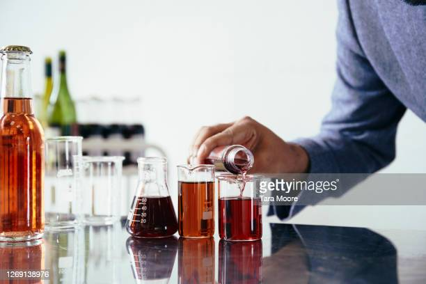man pouring wine into beakers - liquid stock pictures, royalty-free photos & images