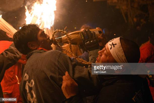 A man pours a bottle of sake into his friends mouth during the Nozawaonsen Dosojin Fire Festival on January 15 2018 in Nozawaonsen Japan The festival...