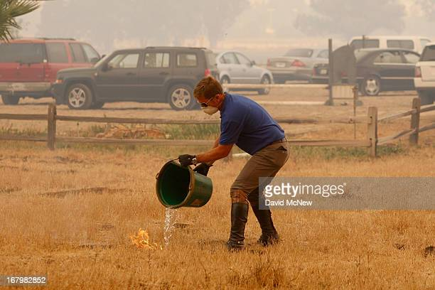 A man pours a bucket of water on a spot fire as a main fire front approaches the Blackiston Ranch as the Springs fire continues to grow on May 3 2013...