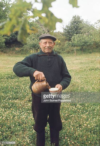 A man pours a cup of cider in Brittany northern France circa 1970