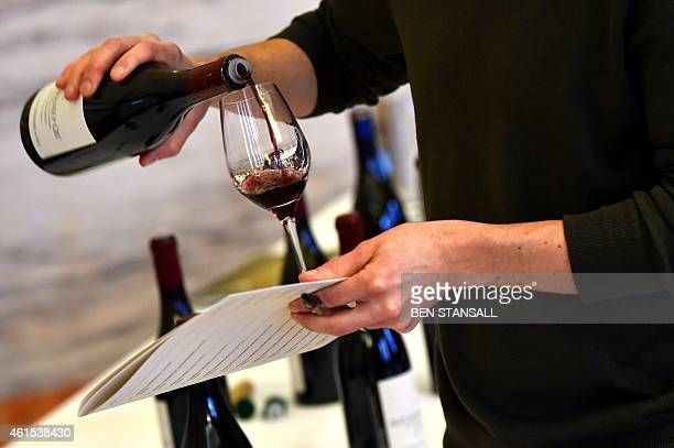 A man pours a glass of wine for tasting during the Burgundy Week showcase at the Institution of Civil Engineers in London on January 13 2015 Twenty...