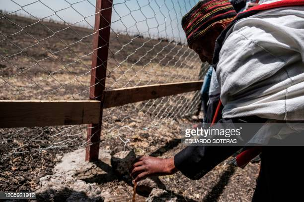 A man pours a traditional beverage into the ground a part of a memorial ceremony at the crash site of the Ethiopian Airlines Flight 302 airplane...