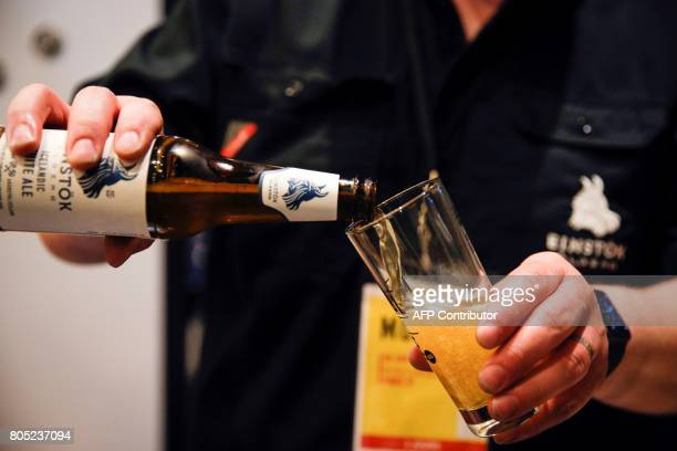 A man pours beer from an icelandic handmade brewery into a glass during the festival Mondial de la Biere on June 30 2017 in Paris The event runs from...