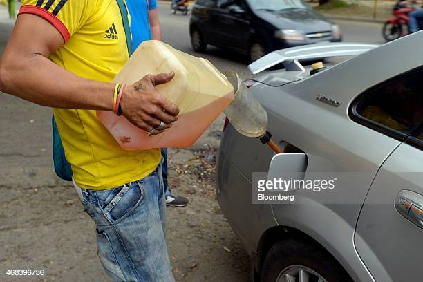 A man pours black market gasoline into a customer's car on the street in Cucuta Colombia on Tuesday Feb 24 2015 Colombians in Cucuta on the border...