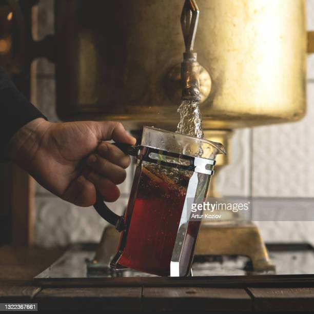 man pours boiling water from antique copper samovar into modern glass teapot. retro style. vintage image. close up shot - third place stock pictures, royalty-free photos & images