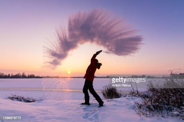 man pours boiling water into the air in the bitter cold. outdoor winter fun - ukraine stock pictures, royalty-free photos & images