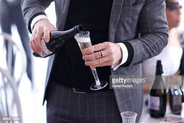 A man pours champagne during the Men's Myer Fashions on the Field on AAMI Victoria Derby Day at Flemington Racecourse on November 4 2017 in Melbourne...