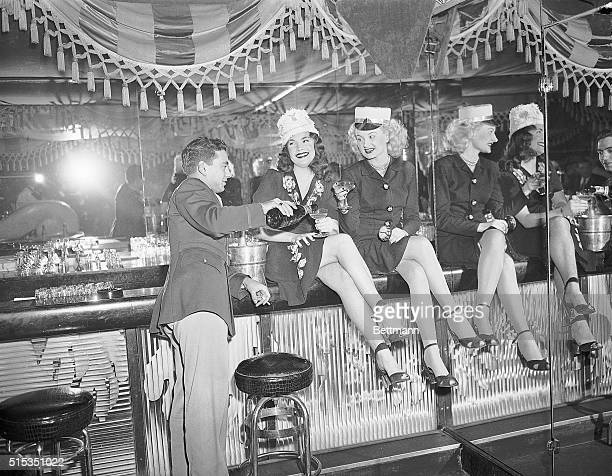 A man pours champagne for two women seated on the bar at the Diamond Horseshoe during a New Year celebration