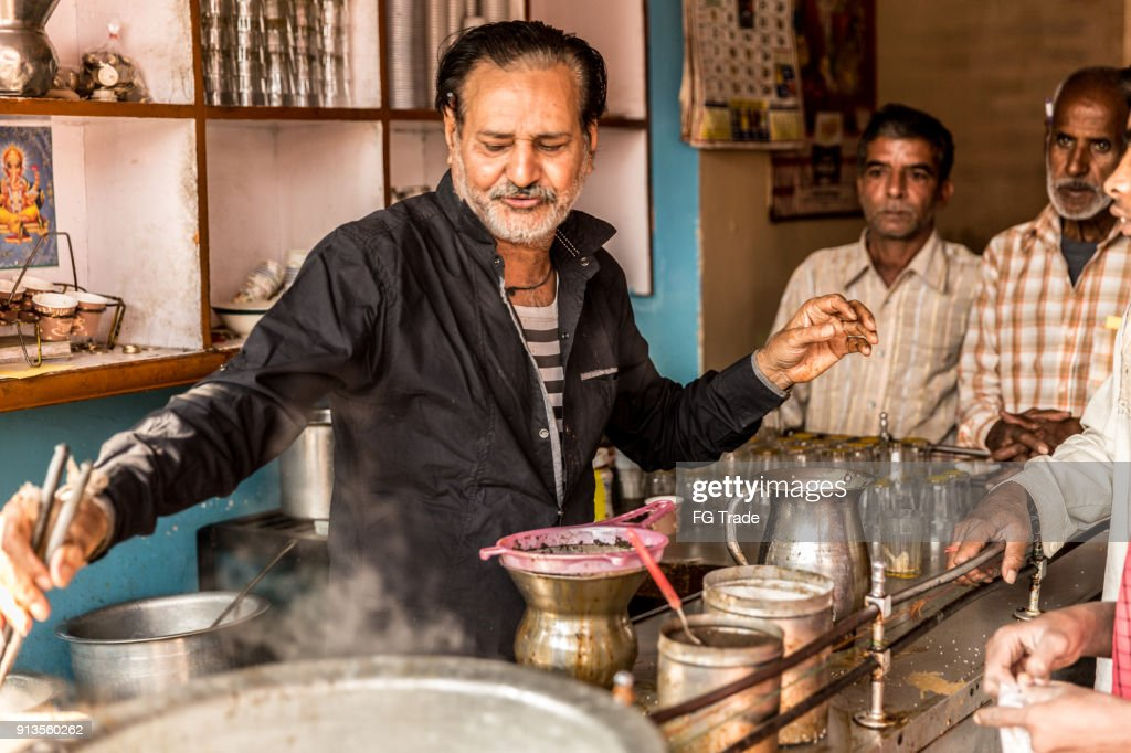 Man pours cup hot milk tea (Masala Chai) Indian style : Stock Photo
