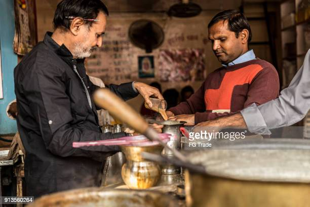 Man pours cup hot milk tea (Masala Chai) Indian style