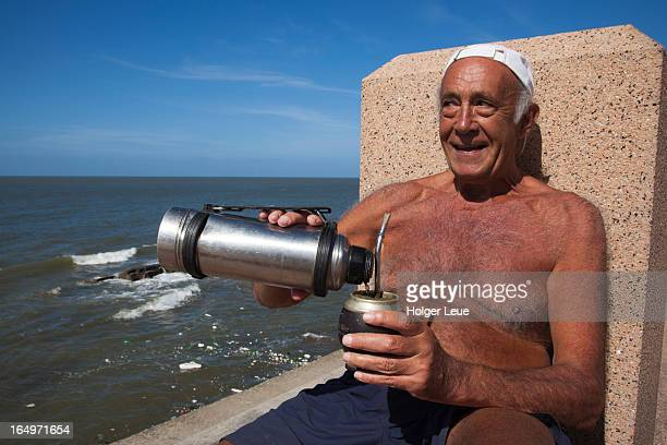 Man pours cup of mate from thermos