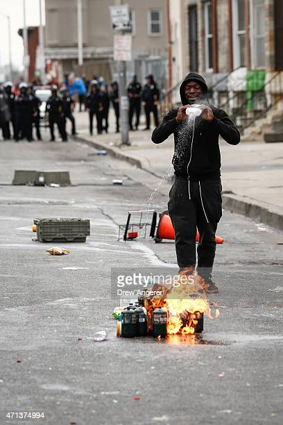 A man pours lighter fluid on debris near the intersection of Pennsylvania Avenue and North Avenue April 27 2015 in Baltimore Maryland Riots have...