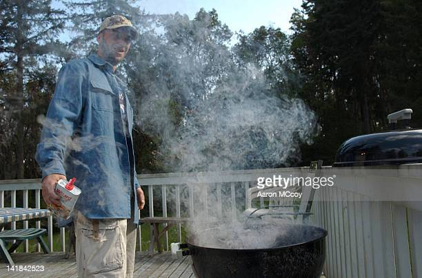 Man pours lighter fluid onto BBQ