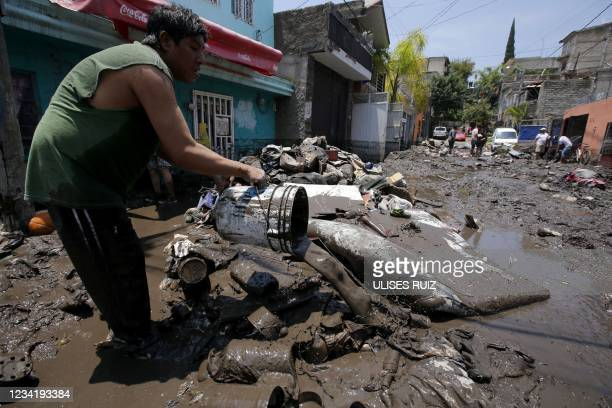 Man pours mud on a street as he tries to clean his house after heavy rains overflowed the El Seco stream, in Zapopan, Jalisco state, Mexico, on July...