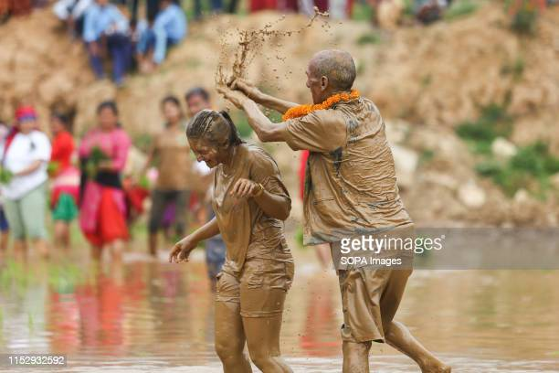 A man pours muddy water onto a lady during a Festival Farmers celebrate National Paddy Day Festival on 'Asar 15' of the Nepali calendar as the annual...