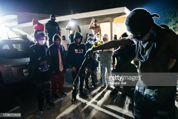 Man pours out an alcohol beverage on a site where a demonstrator was killed on August 26, 2020 in Kenosha, Wisconsin. On August 25, 17-year-old Kyle...