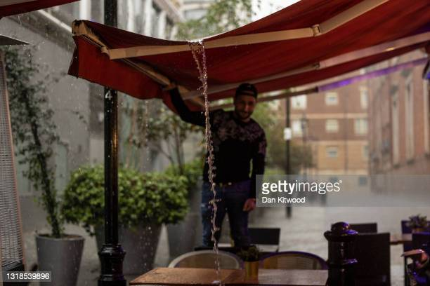 Man pours rain water from an awning at a restaurant in Soho on May 17, 2021 in London, United Kingdom. From today, covid restrictions on indoor...