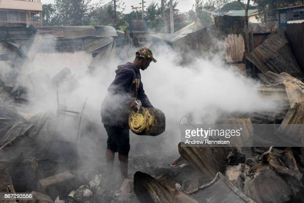 A man pours water on burning ruins of Kikuyu homes and shops which were destroyed in the Kawangware slum on October 28 2017 in Nairobi Kenya Protests...