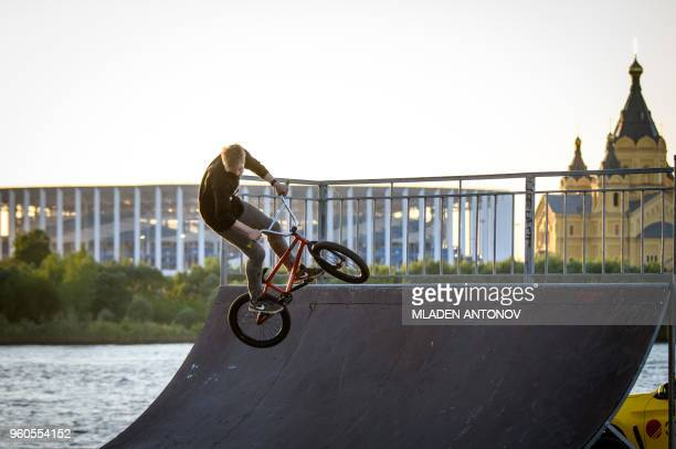 A man practices BMX in front of the Nizhny Novgorod Arena and Alexander Nevsky Cathedral in Nizhny Novgorod on May 20 2018 Nizhny Novgorod stadium...