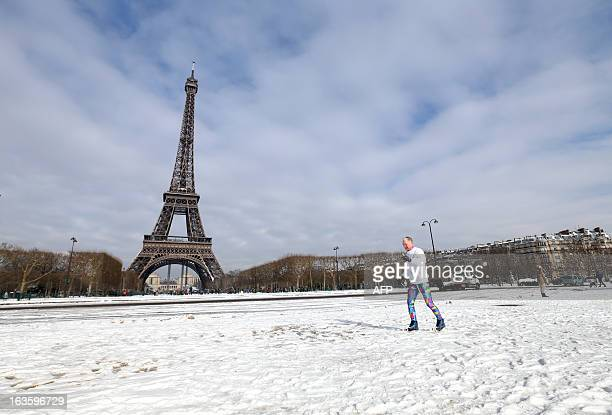A man practices crosscountry skiing during a snowy day on the ChampdeMars near the Eiffel tower on March 13 2013 in Paris Blizzardlike conditions...