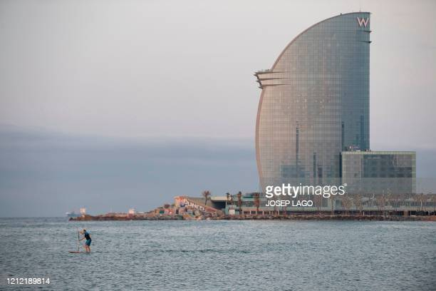 Man practices paddle surfing at La Barceloneta Beach in Barcelona, on May 8 opened for the first time since Spain declared a state of emergency due...