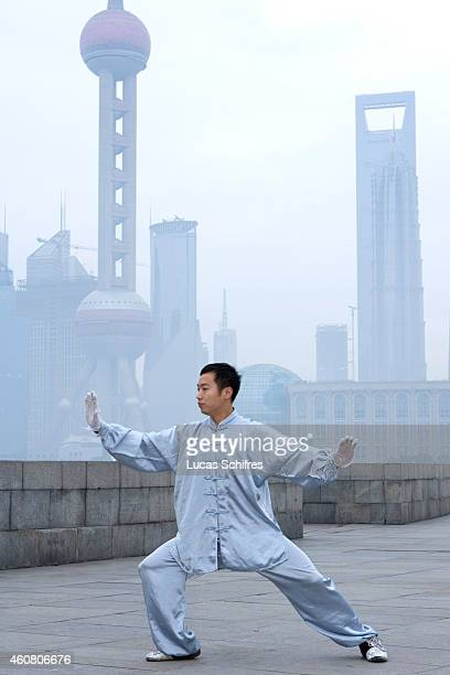 A man practices the Chinese martial art taichi at dawn on the Bund on February 1 2009 in front of the Oriental Pearl tower and the World Financial...