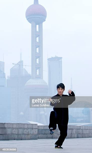 A man practices the Chinese martial art taichi at dawn on the Bund on February 1 2009 in front of the Oriental Pearl tower Shanghai China