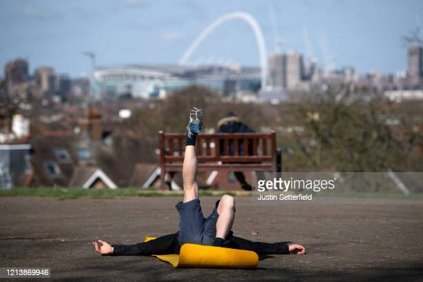 Man practices yoga in the park in front of Wembley Stadium on March 21, 2020 in London, England. Londoners are feeling the impact of shutdowns due to...