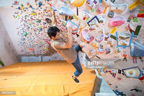 A man practicing at a bouldering gym.