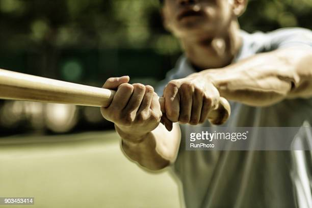 man practicing baseball bat swing - baseball bat stock pictures, royalty-free photos & images