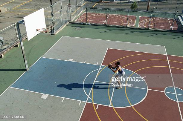 man practicing free throws on outdoor basketball court, elevated view - making a basket scoring stock photos and pictures