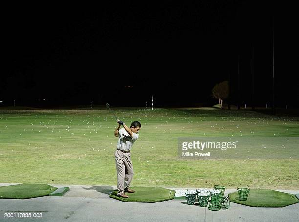 man practicing golf on  driving range at night - practicing stock pictures, royalty-free photos & images