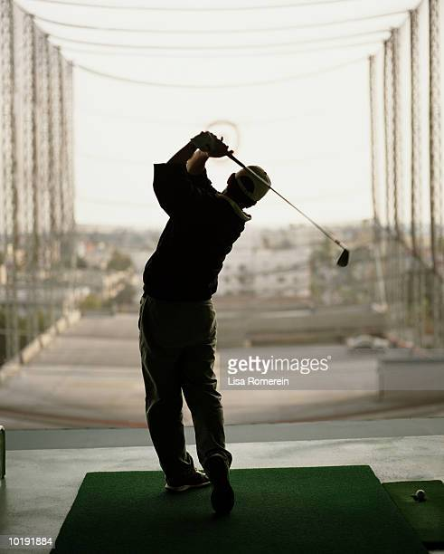 man practicing golf swing in driving range, rear view - driving range stock pictures, royalty-free photos & images