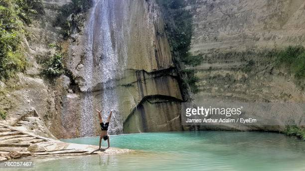 Man Practicing Handstand Against Waterfall
