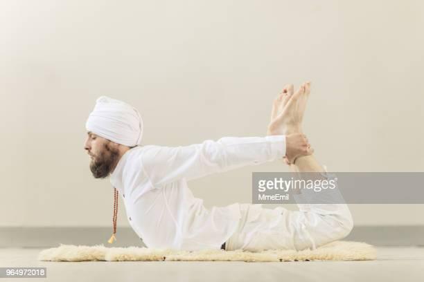 man practicing kundalini yoga and bow pose - yogi stock photos and pictures