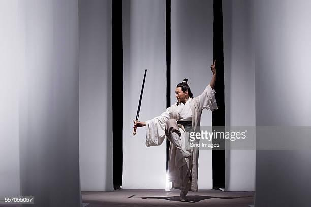 man practicing martial arts in ancient costumes - kung fu fotografías e imágenes de stock
