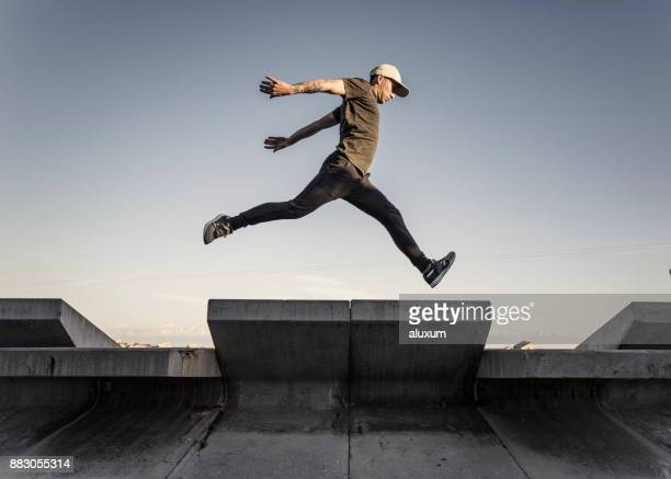 man practicing parkour in the city - vita cittadina foto e immagini stock