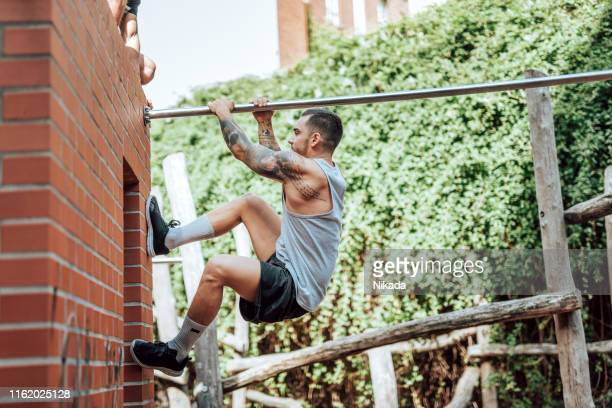 man practicing parkour in urban space - stunt person stock photos and pictures