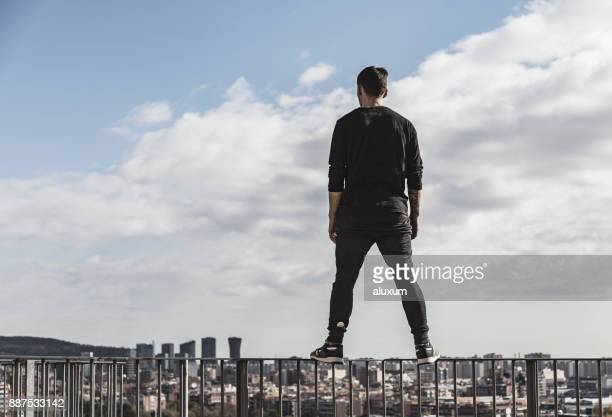 man practicing parkour. view of hospitalet and barcelona from cornella de llobregat catalonia spain - free running stock pictures, royalty-free photos & images