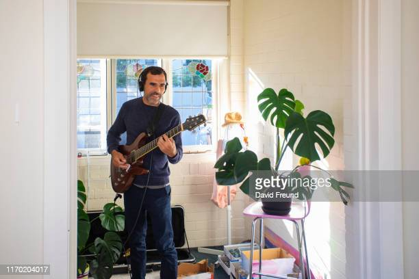 man practicing playing electric guitar at home - david freund stock pictures, royalty-free photos & images