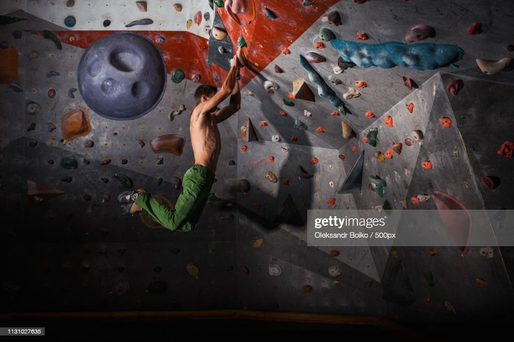 Man Practicing Rock-Climbing On A Rock Wall Indoors : Photo