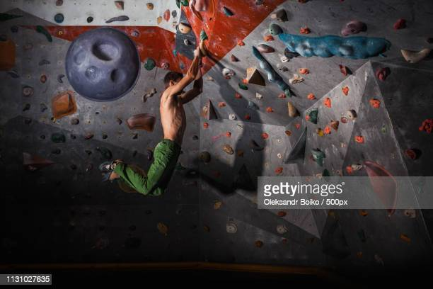 Man Practicing Rock-Climbing On A Rock Wall Indoors