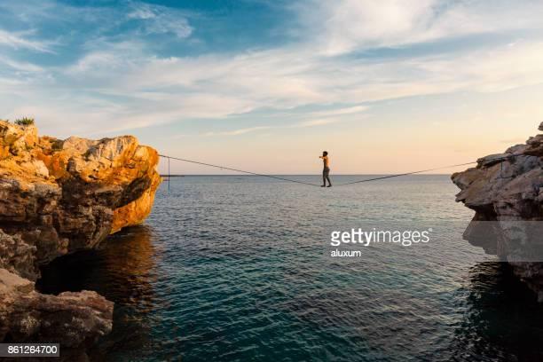 Man practicing slackline over the sea