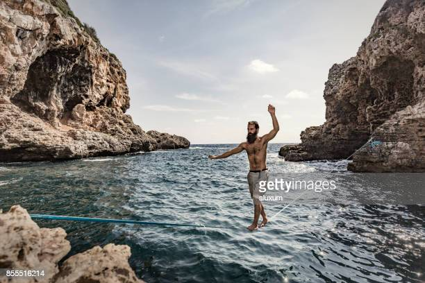 Man practicing slacklining over the sea