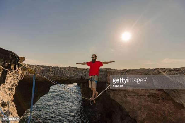 Homme de pratiquer le slackline au-dessus de la mer