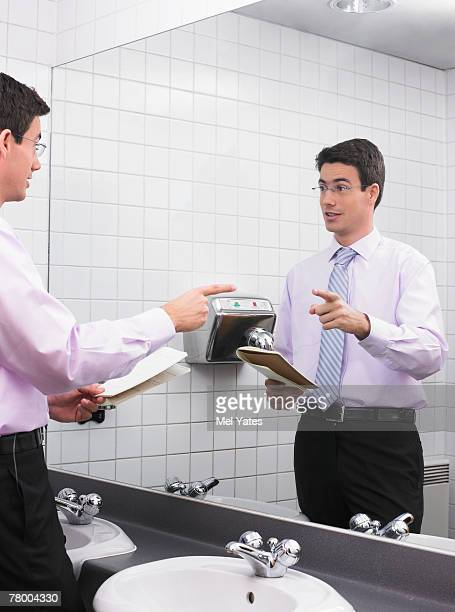 man practicing speech in office washroom mirror - vanity mirror stock photos and pictures